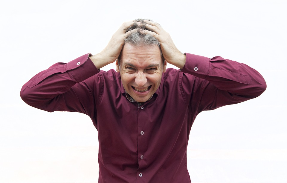 man stressed and covering his ears from the noise